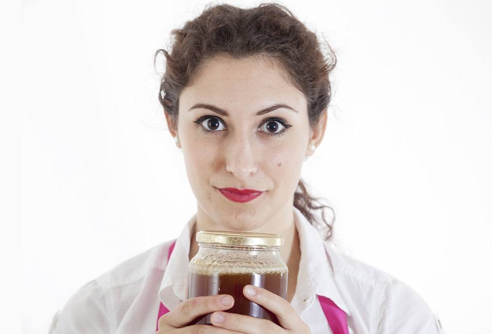 woman with a jar of honey in her hands