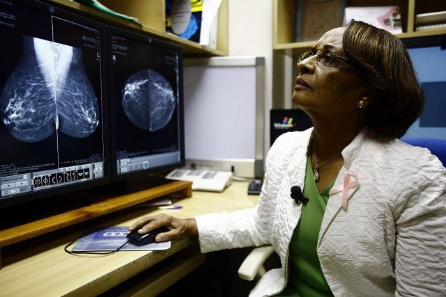 A radiologist looking at a screen.