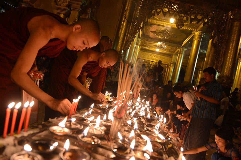 Buddhist monks lighting candles