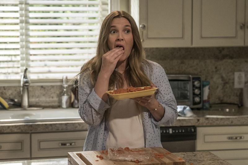 Drew Barrymore eats in a kitchen in a scene from Netflix's Santa Clarita Diet