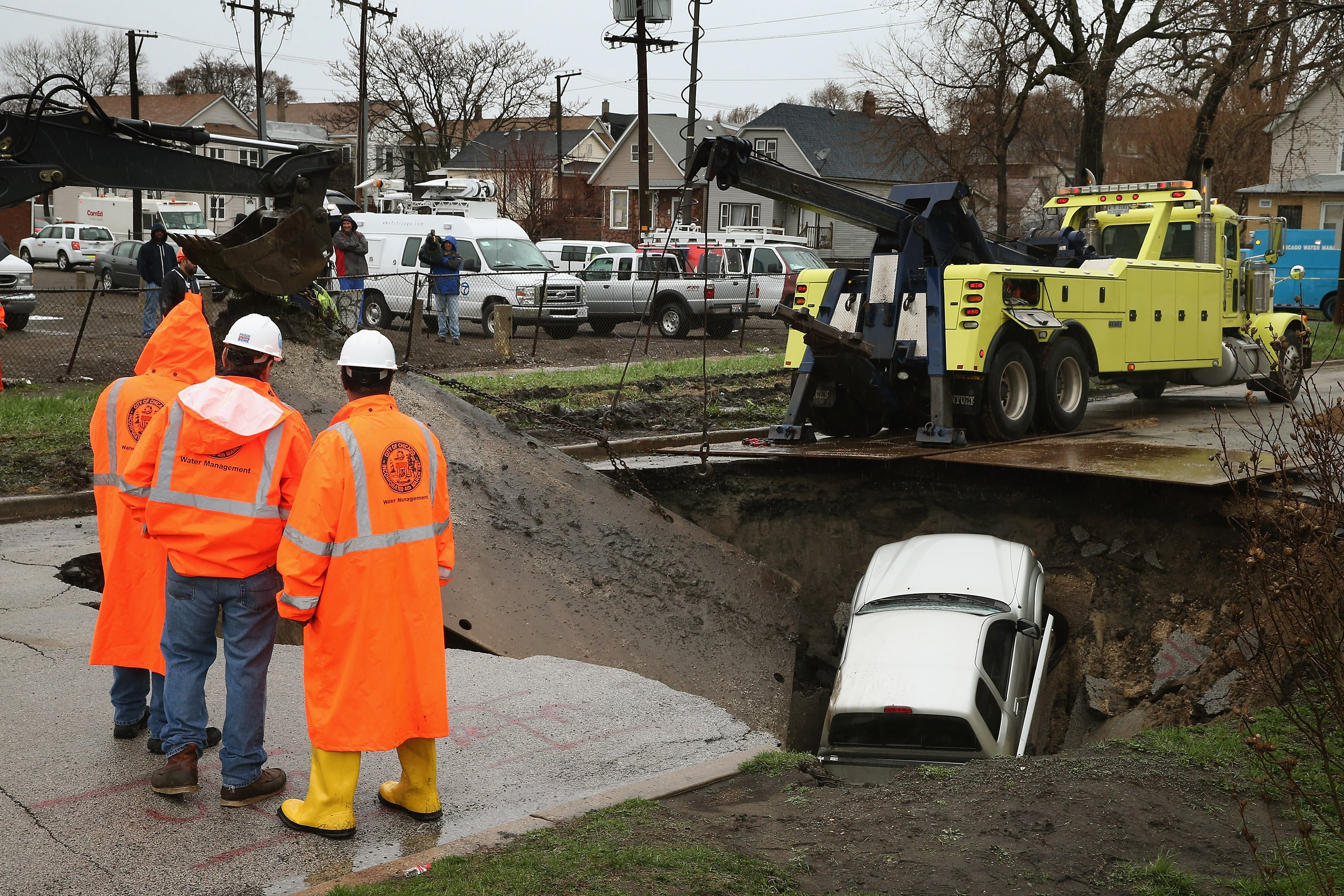Workers prepare to pull a truck from a sinkhole