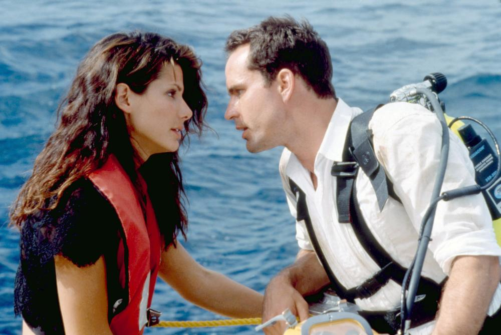 Sandra Bullock and Jason Patrick floating together in the ocean, about to kiss