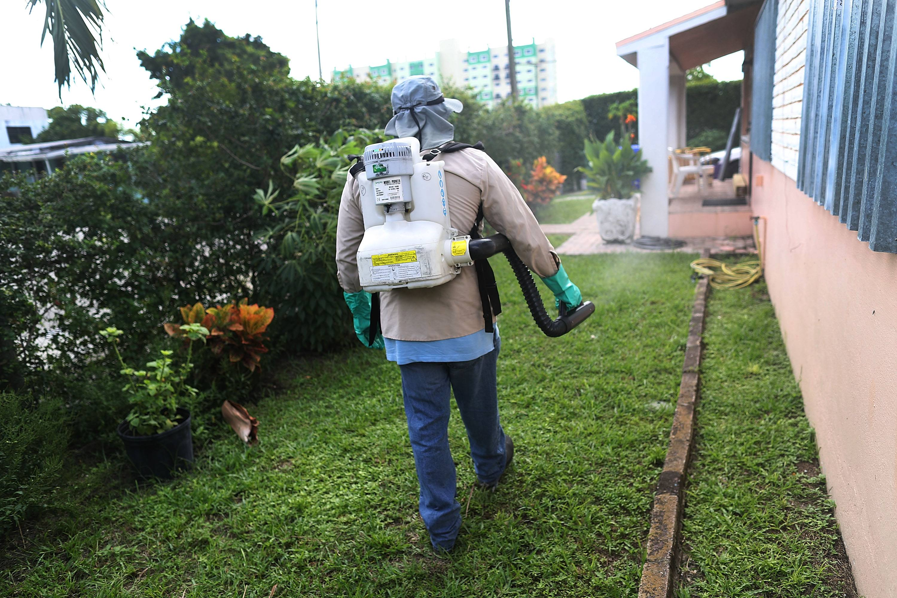 A man sprays pesticide around a building