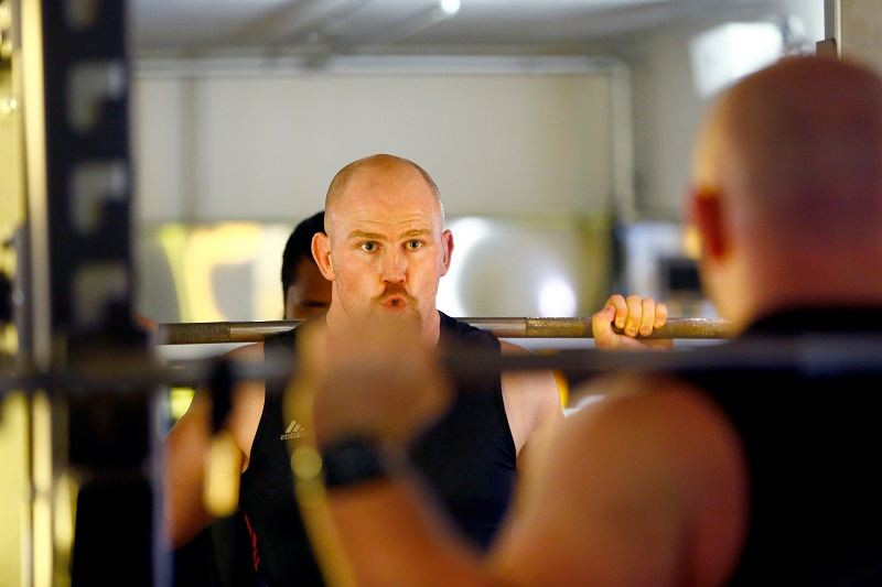 A man pursuing his fitness goals by doing squats at the gym