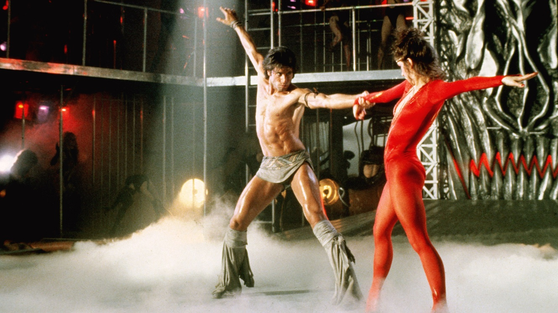 A shirtless John Travolta dances with Cynthia Rhodes on a smokey dancefloor