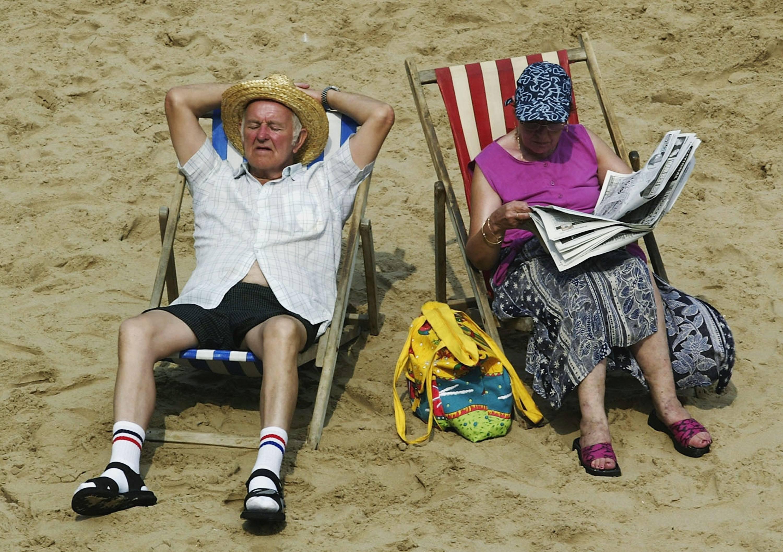 Retirees enjoy retirement by sunbathing on the beach