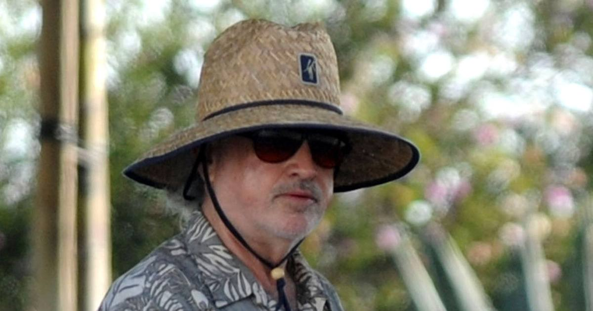 Terrence Malick wearing a wide-brimmed straw hat and sunglasses