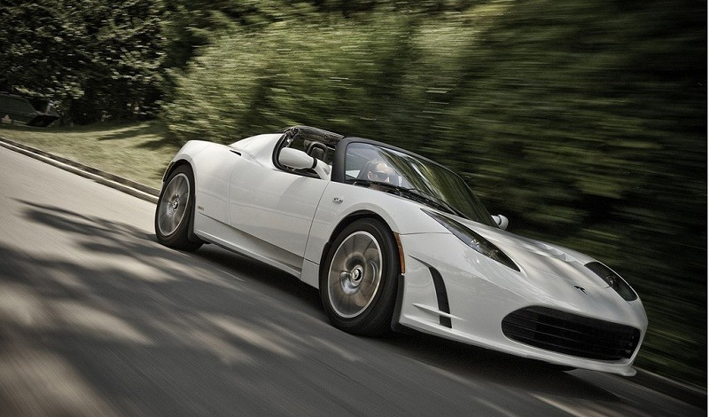 A Tesla Roadster in white speeding down the road