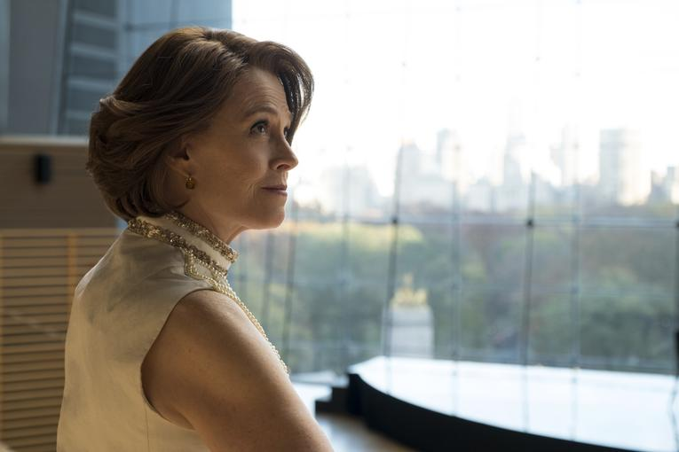Sigourney Weaver sitting at a desk with a view of the city outside in The Defenders