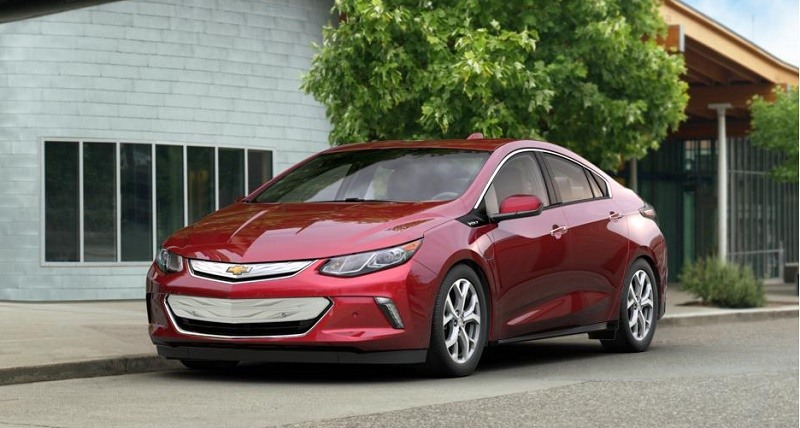 A red 2017 Chevrolet Volt sits parked in front of a house