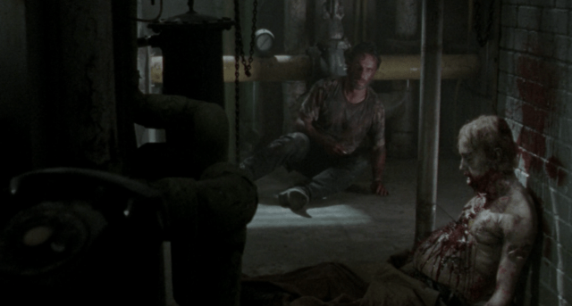 """Rick sits near the zombie that ate Lori in a scene from the Season 3 'Walking Dead' episode """"Say The Word"""""""