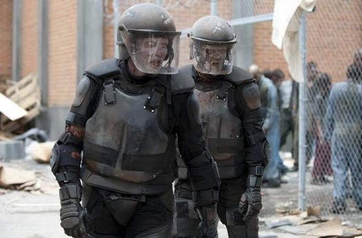 Two walkers wearing riot gear walk in the prison grounds in an episode of 'The Walking Dead'