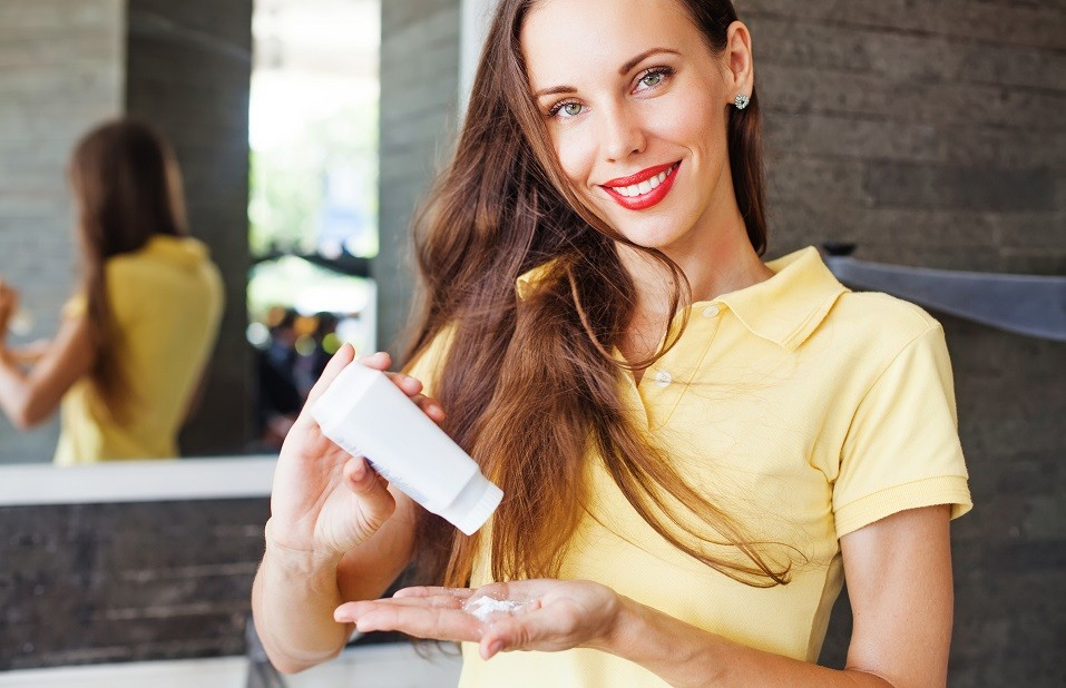 woman applying dry shampoo