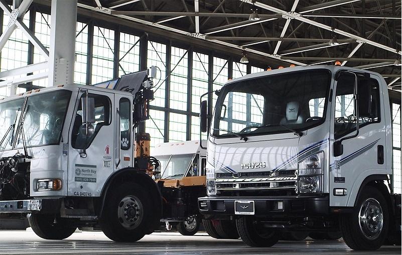 White Wrightspeed trucks sit parked in a garage