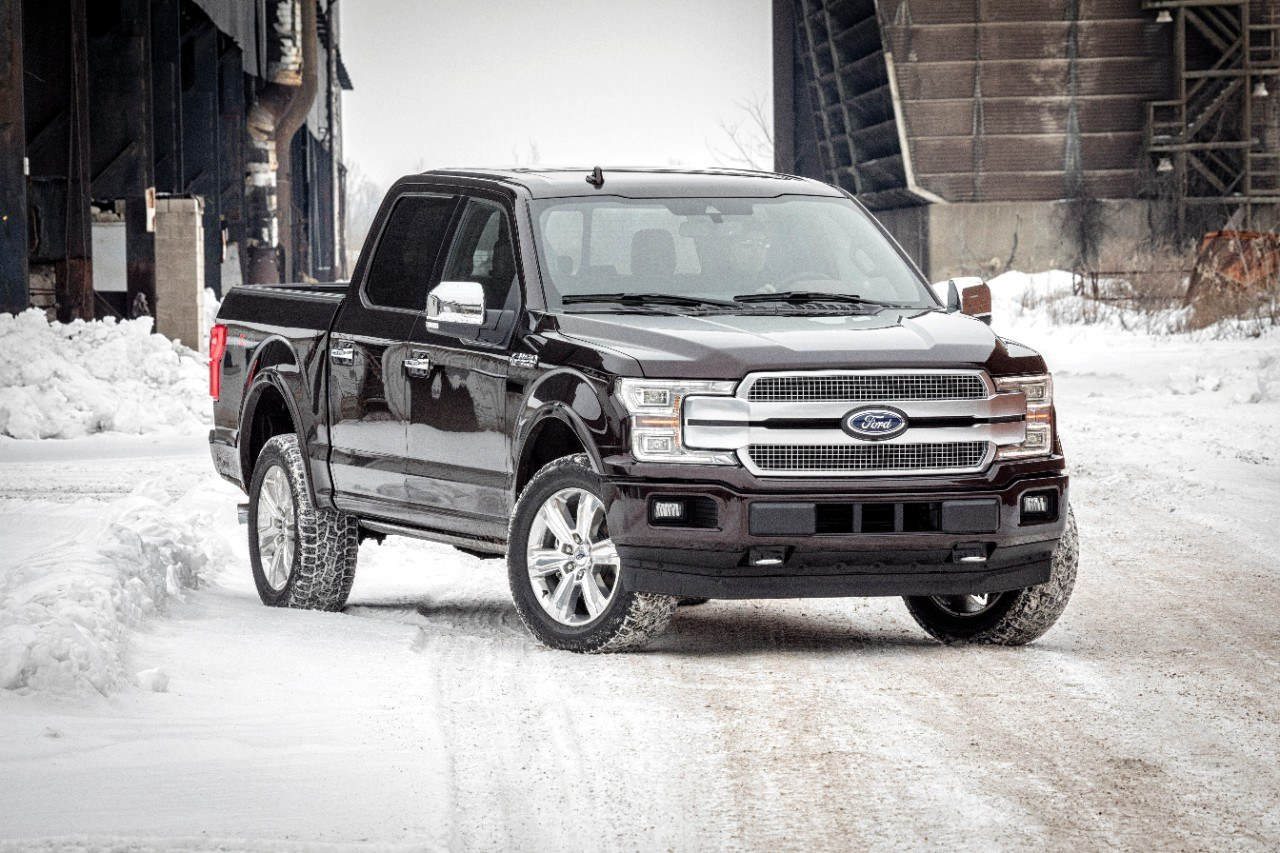 The Ford F-150 in black parked on a snowy road.