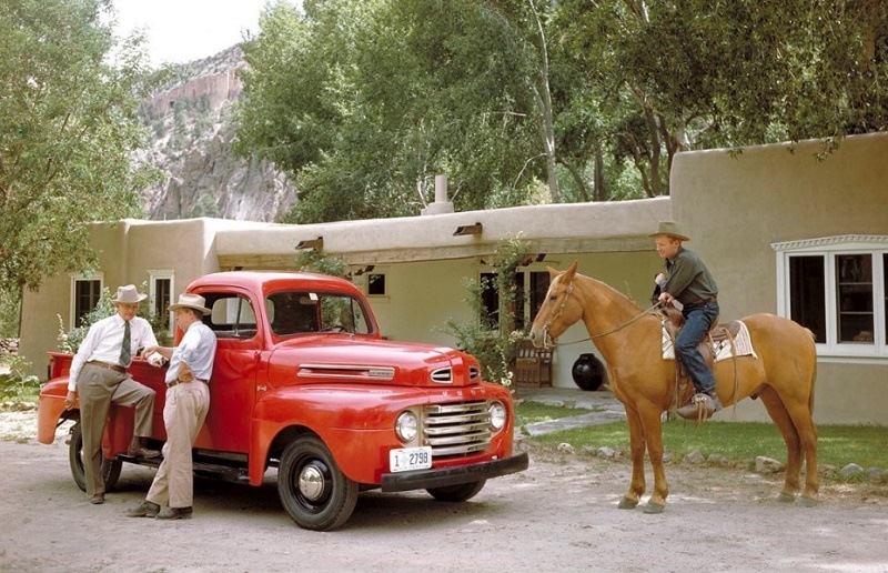 Two men wearing cowboy hats lean on a red Ford F-1 truck as it sits parked in front of a house