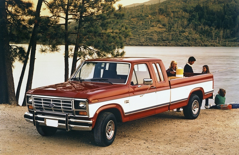 F-150 from 1985 sits parked in front of a lake