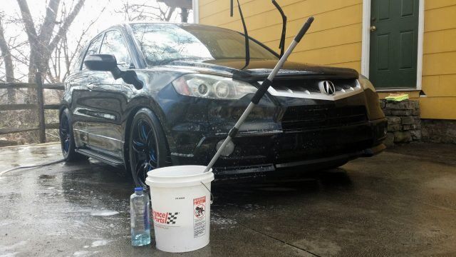 a car on a driveway next to a bucket of cleaning solution