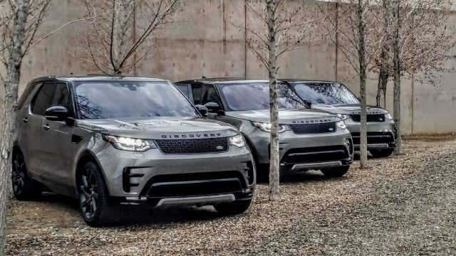 Three Land Rover Discovery vehicles parked in a forest