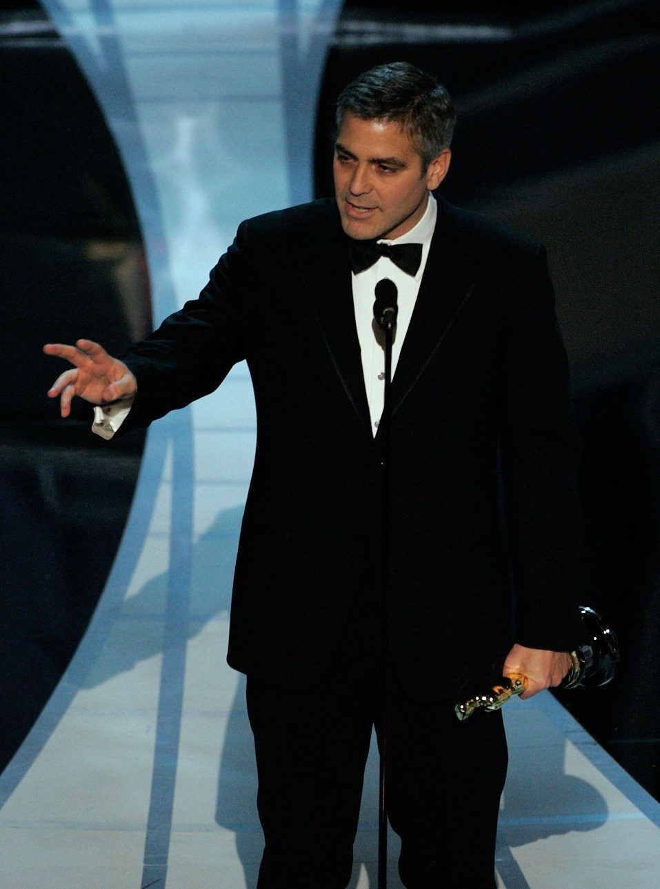 Actor George Clooney accepts the Best Supporting Actor award on stage during the 78th Annual Academy Awards
