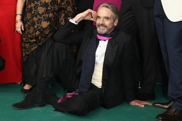 Actor Jeremy Irons sits on the ground in front of a group of people