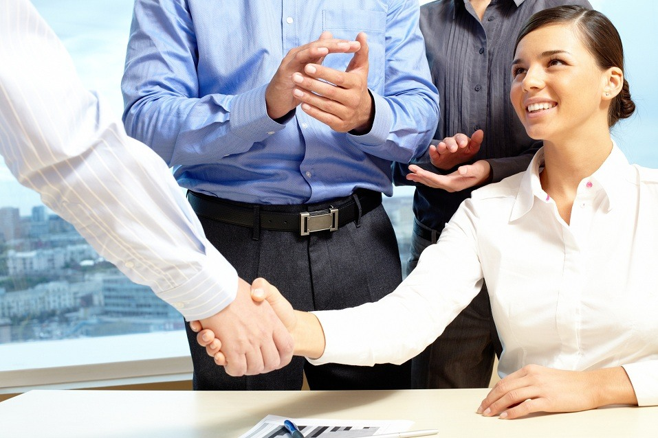 A woman shakes hands with a colleague