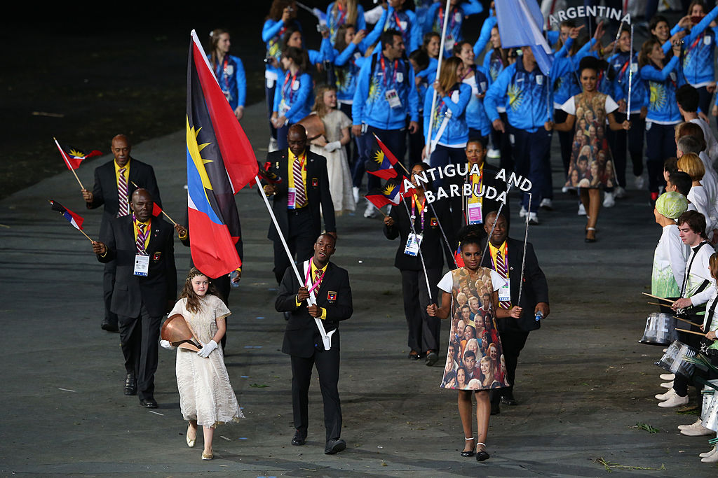 Daniel Bailey of the Antigua and Barbuda Olympic athletics team carries his country's flag