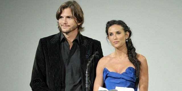 Demi Moore and Ashton Kutcher stand side by side at a podium.