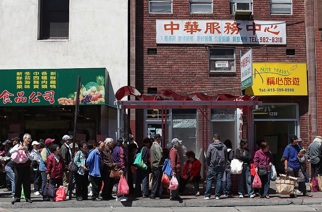 People wait for a bus in Chinatown