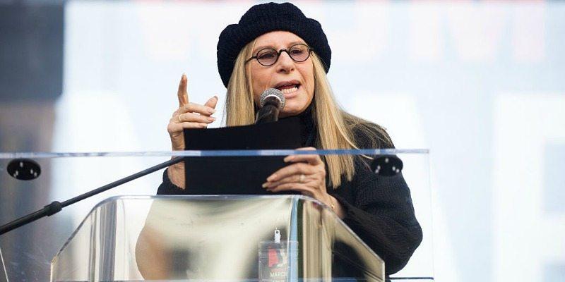 Barbra Streisand talking at a podium while wearing black