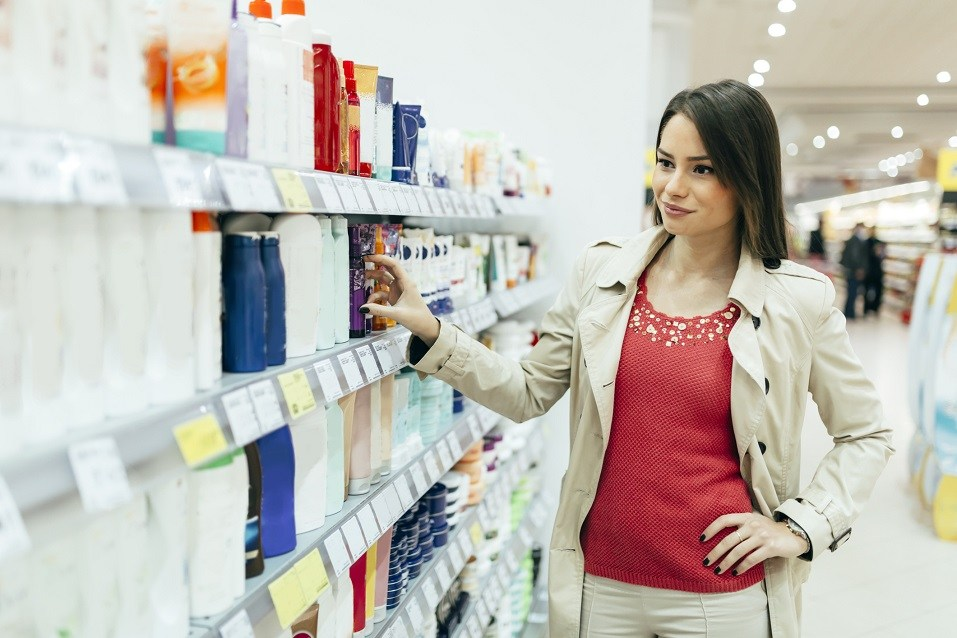 woman buying body care products in supermarket