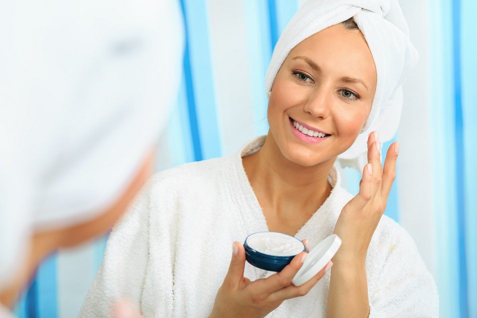 Woman in a bathrobe applying products to her skin