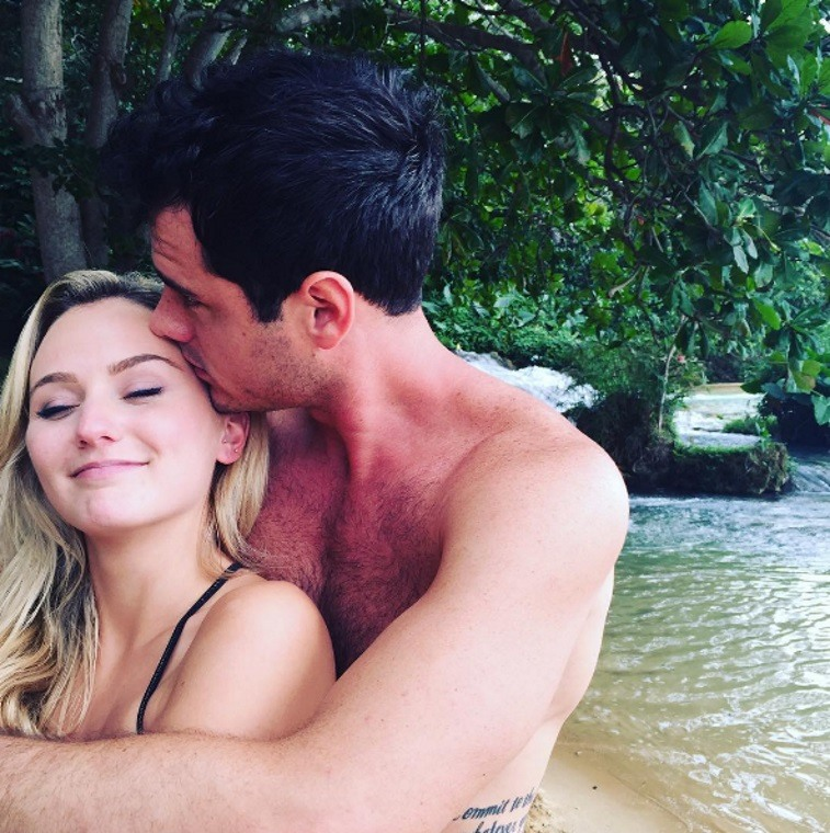 Ben Higgins is kissing Laura Bushnell head and has his arms around her.