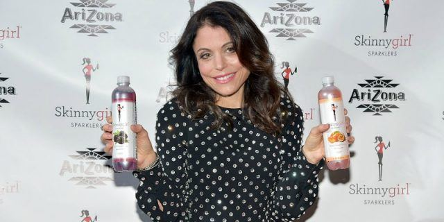 Bethenny Frankel holding up two bottles of drinks.