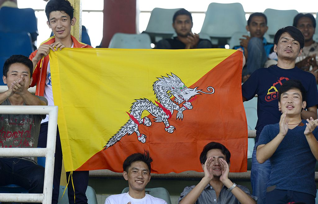 Bhutanese football supporters hold their national flag
