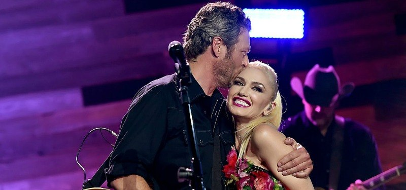 Blake Shelton kisses Gwen Stefani on the head as she smiles.