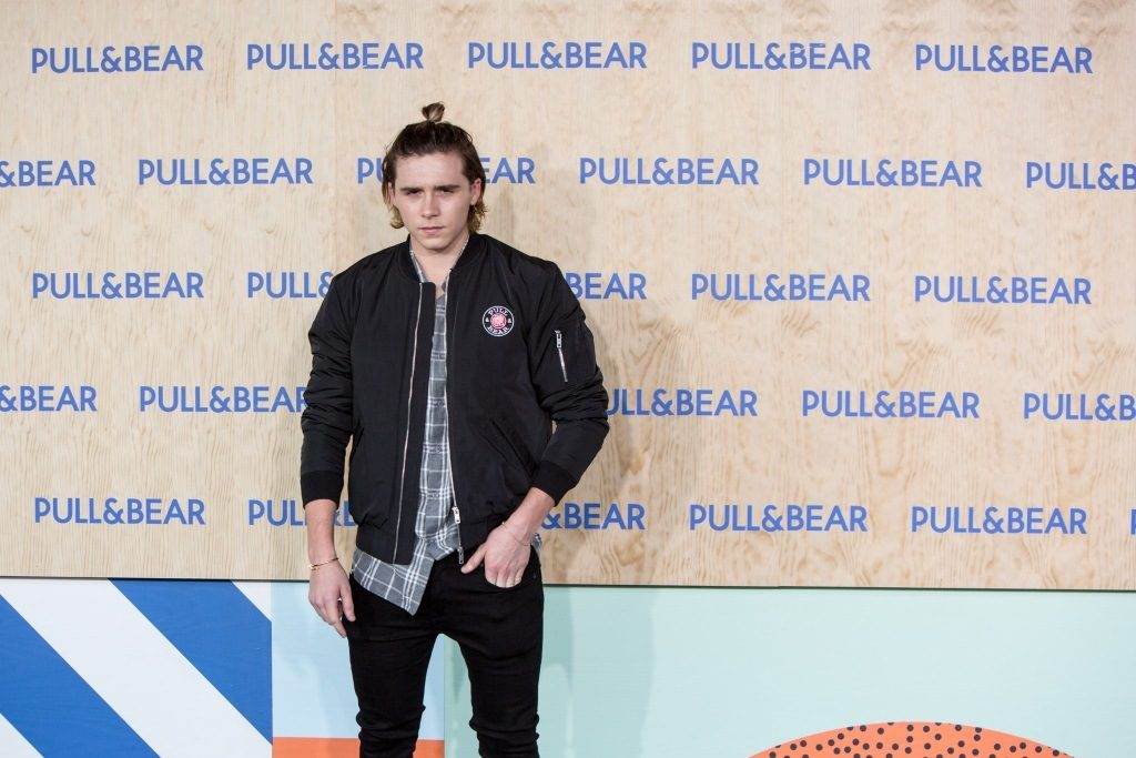 Brooklyn Beckham poses on the red carpet and has a man bun.