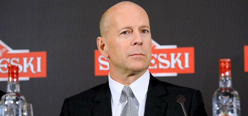 Bruce Willis sitting in front of two bottles of Sobieski