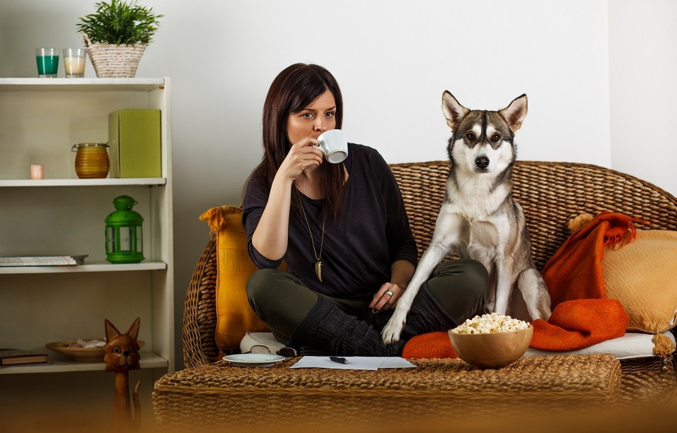 Young woman drinks her coffee on the couch alongside her dog