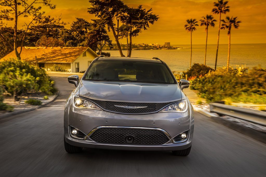 Front view of 2017 Chrysler Pacifica on street lined with palm trees