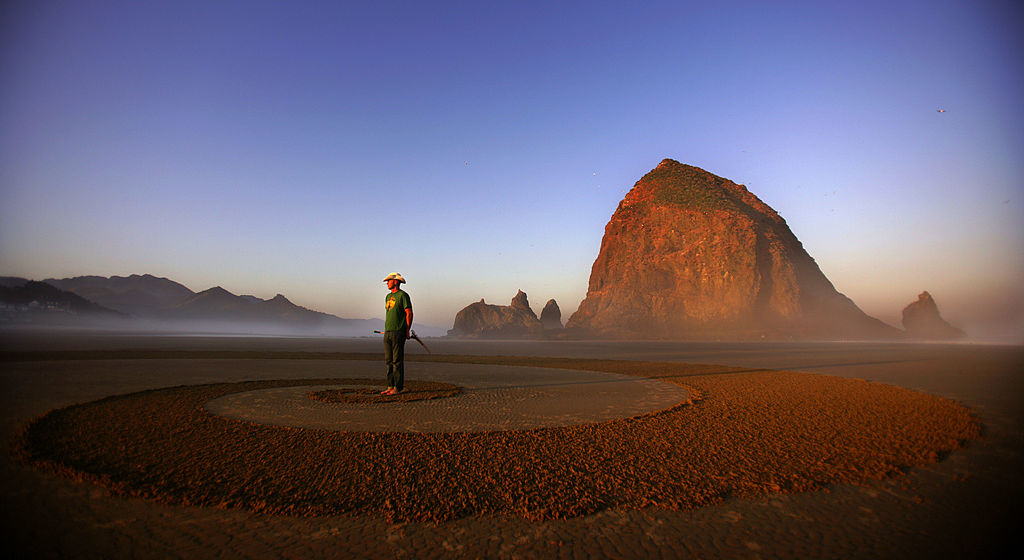 An artist stands on the sand in Cannon Beach, Oregon