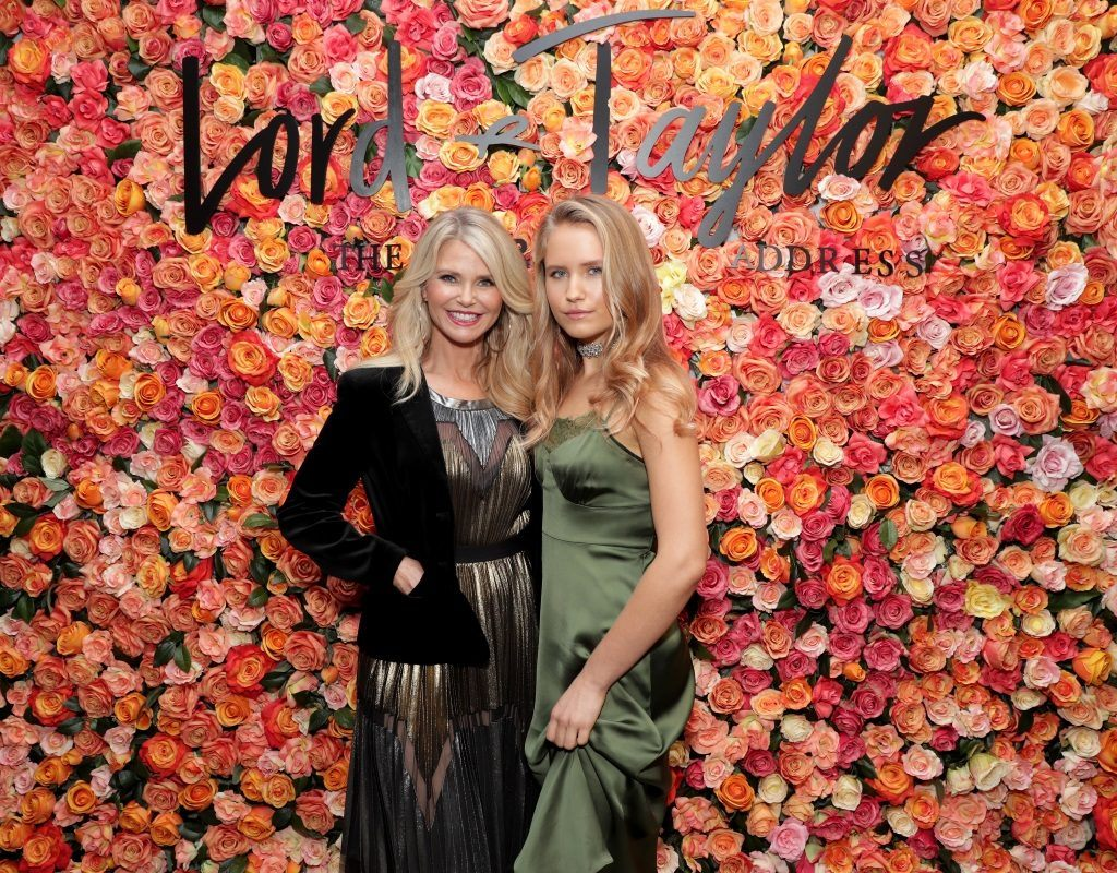 Sailor and Christie Brinkley pose together in front of a rose wall.
