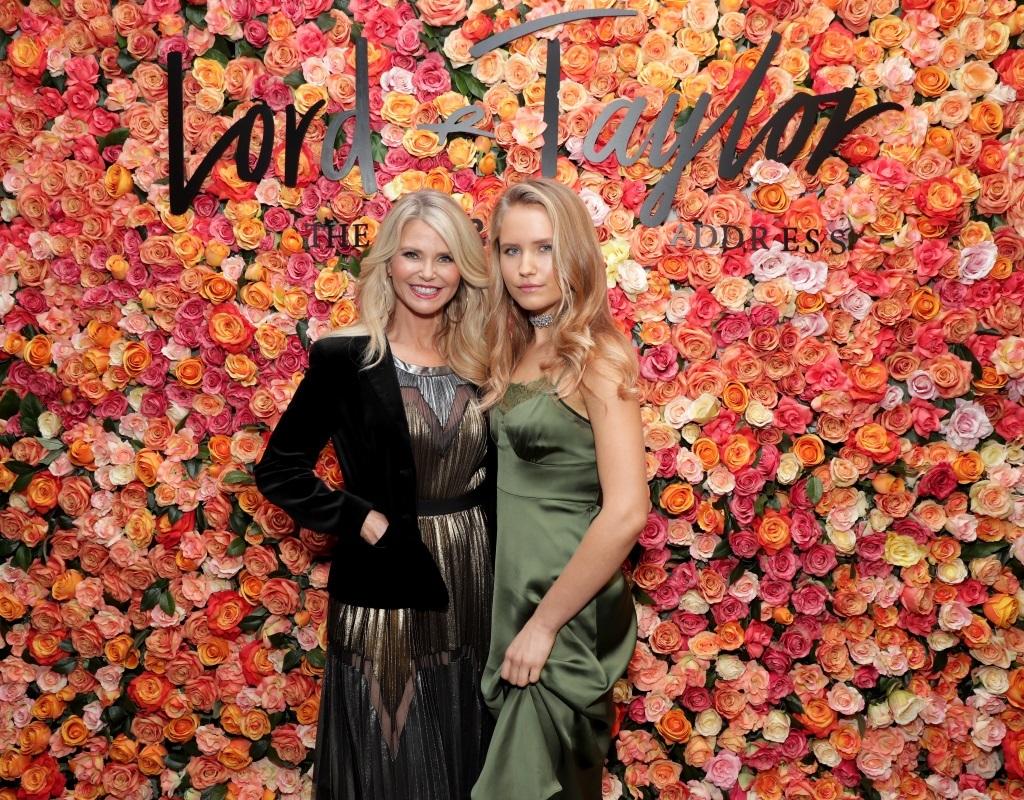 Sailor Brinkley and Christie Brinkley pose together in front of a floral background.