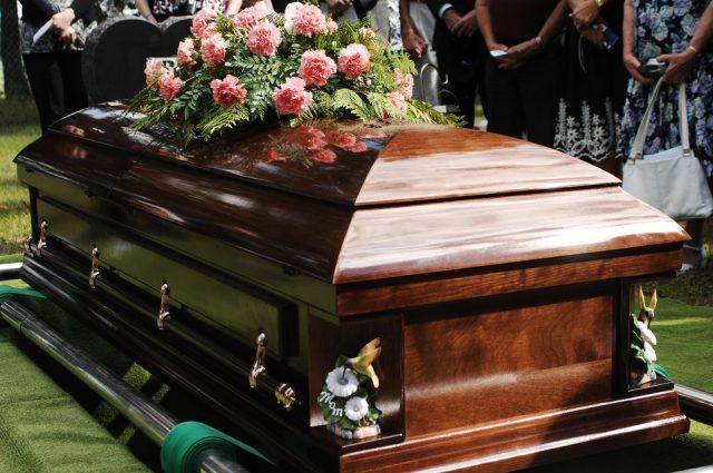 A coffin about to be lowered at a funeral service