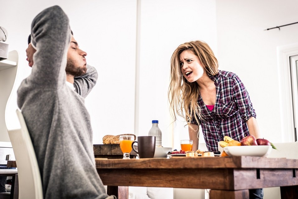 A man flings his arms over his head in exasperation as his partner yells at him in the dining area of their kitchen
