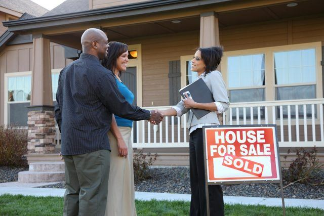Couple shake hands with real estate agent