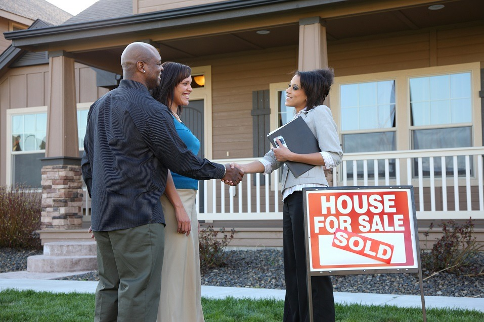 Couple shakes hands with Realtor.