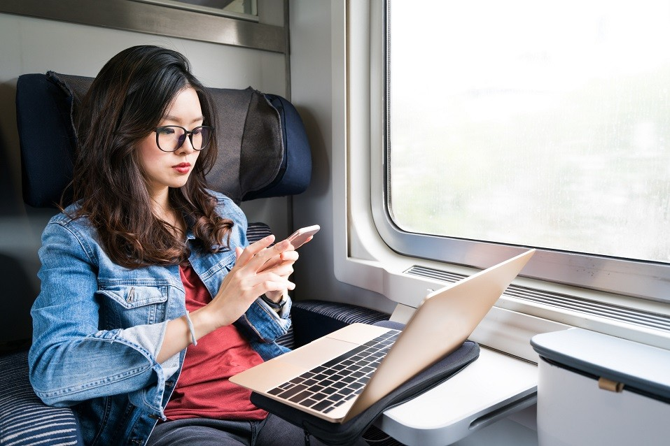 woman using smartphone and laptop on train