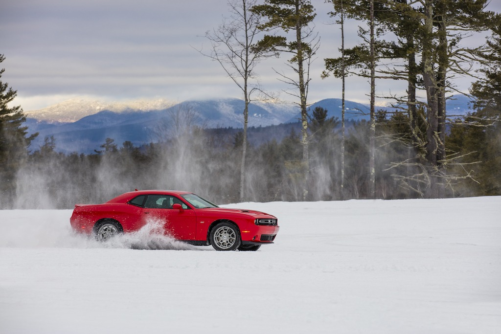 A red 2017 Dodge Challenger GT AWD drives in the snow