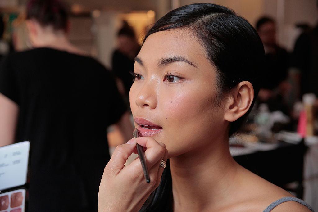 Backstage a model gets makeup applied before the David's Bridal Spring/Summer 2017